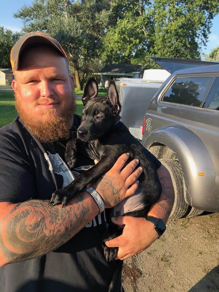 jake robinson carrying a black puppy